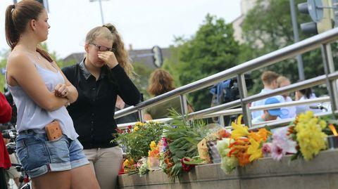 Una joven llora de emoción junto a las flores depositadas en la entrada del centro comercial Olympia