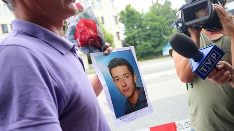 El padre de unas de las víctimas posa con la fotografía de su hijo