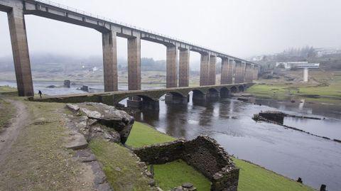 El bajo nivel del agua en el embalse de Belesar, Portomarín, deja al descubierto el viejo puente