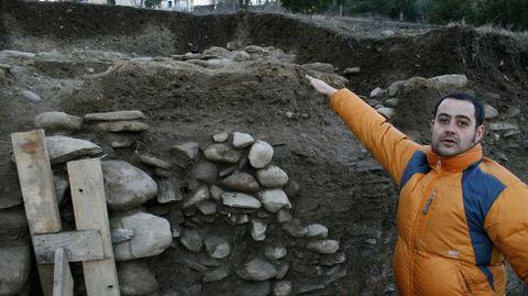 O arqueólogo Iván Álvarez Merayo mostra unha das estruturas aterrazadas da ladeira do monte de San Vicente sobre as que se levantaron as vivendas do castro