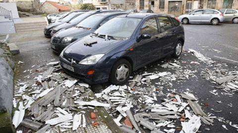 Destrozos en varios coches por la caída de una medianera en Pontevedra.