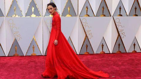 Ruth Negga lució un fabuloso vestido con cola, de manga larga y cuello de encaje con reminiscencias isabelinas firmado por Valentino, un modelo rojo que conjuntaba con tiara y pendientes granates