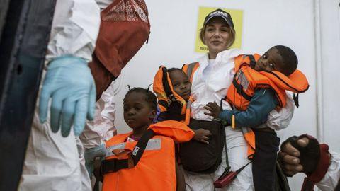 Una voluntaria de la ONG MOAS sostiene en sus brazos a dos pequeños rescatados del mar Mediterráneo