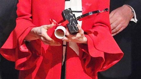El abrigo, de color rojo, tiene cuello redondo y manga larga con detalle de volantes en puño. El eetalle más destacado de su diseño.