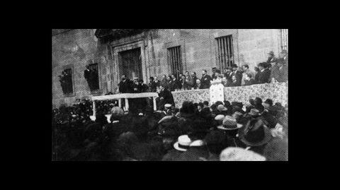 Un mitin ante la fachada del colegio en una fotografía de 1918