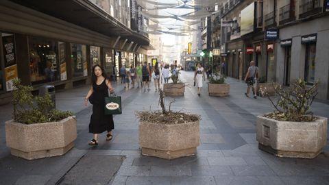 Viandantes caminan por la Calle Preciados de Madrid, una de las vías comerciales más concurridas de la capital, donde hoy se han colocado jardineras para evitar el tránsito de vehículos después de los atentados ocurridos