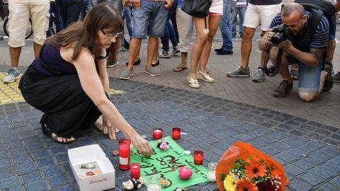 Muchas personas han empezado a depositar mensajes y velas en el mosaico en las Ramblas de Barcelona después del atentado ocurrido ayer