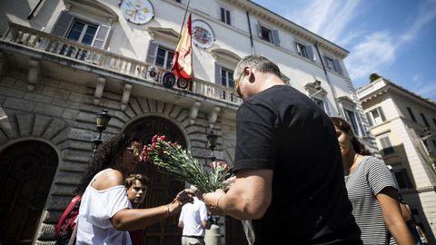 Varias personas prepararan flores para colocarlas en la puerta de la embajada española en la Santa Sede en Roma