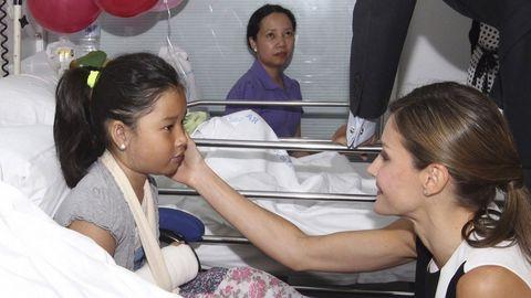 La Reina Letizia acaricia a una niña herida en el atentado durante la visita que los reyes realizaron ayer al Hospital del Mar