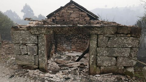 Incendio forestal con casas quemadas en As Mestas