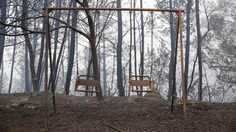 Incendio forestal con casas quemadas en As Fermosas
