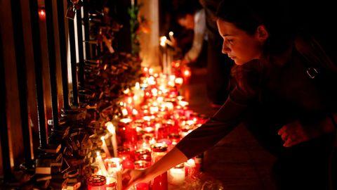 Una mujer coloca una vela en el monumento Love durante una vigilia silenciosa a la luz de las velas para protestar contra el asesinato de la periodista
