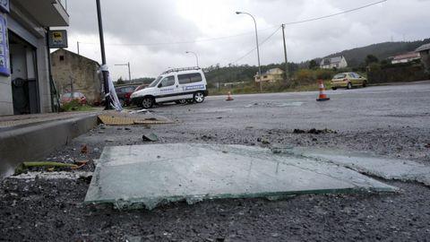 Cristales caídos de una terraza de un piso de Arteixo y los destrozos en varios coches