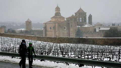 Una pareja pasea delante del Monasterio de Poblet (Tarragona)