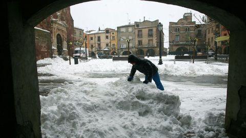 Un vecino retira nieve en la Pl Major de Prades (Tarragona)