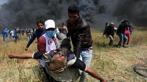 Los manifestantes corren con los heridos entre la intenta humareda dejada por los neumáticos quemados