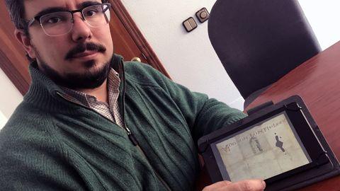 Álvaro Solona, medievalista de la Universidad de Oviedo, muestra un cartel vinculado al Camino del Salvador