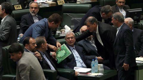 Varios legisladores iraníes conversan con el ministro de Empleo iraní, Ali Rabiei (c), durante el proceso de destitución en el Parlamento iraní en Teherán, Irán. Según fuentes locales, el parlamento votó a favor de la destitución de Rabiej como ministro mientras el país sigue inmerso en una crisis económica.