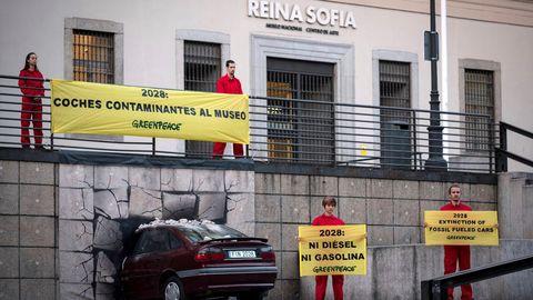 Un coche «empotrado» en un museo para que las emisiones sean historia, una acción reivindicativa de Greenpeace, en la fachada del Reina Sofía de Madrid