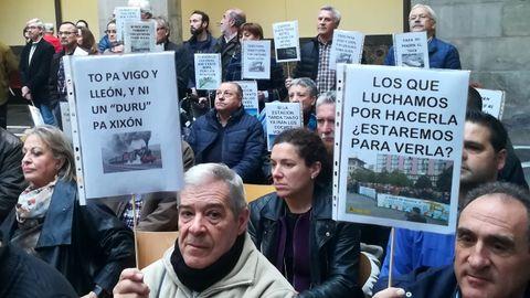 Asistentes a la lectura del manifiesto de la Plataforma en defensa del Plan de Vías con carteles y eslóganes, en el CCAI
