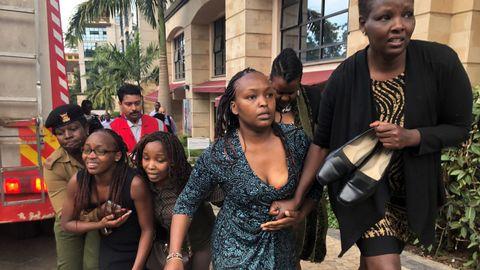 Un grupo de personas buscan refugio en la zona donde se produjo la explosión y los disparos, en un hotel de Nairobi, en Kenia