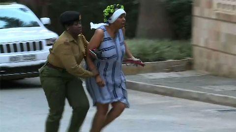 Una mujer huye del lugar donde se produjo la explosión acompañada de un miembro de las fuerzas de seguridad