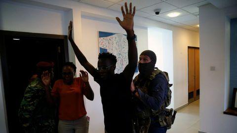 Un grupo de agentes cachean a un hombre en el interior del complejo
