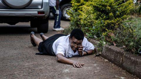 Una mujer se oculta tras un coche en el entorno del hotel