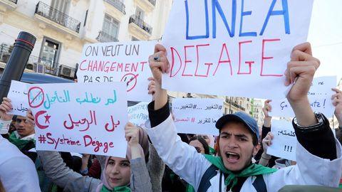 Estudiantes argelinos muestran pancartas en protesta contra el aplazamiento de las elecciones, un día después del anuncio de Buteflika de no optar a un quinto mandato