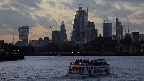 Un barco fluvial cruza el río Támesis mientras el sol se pone en Londres