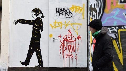 Un hombre camina frente a una pintura que muestra a la primera ministra británica, Theresa May, sonámbula con un pijama negro cubierto de estrellas amarillas similares a las de la bandera de la Unión Europea