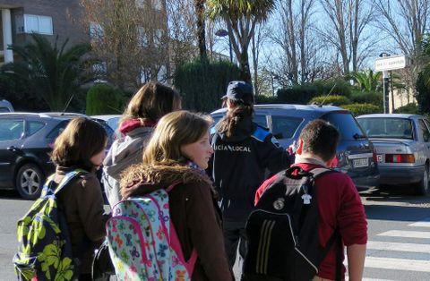 Alumnos cruzan un paso de peatones, en mitad de coches aparcados, en las inmediaciones de un colegio