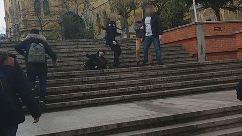 El Policía se gira con el tolete, dejando detrás al herido. A su lado las otras dos personas que han estado a su lado. Uno sujeta del brazo al otro