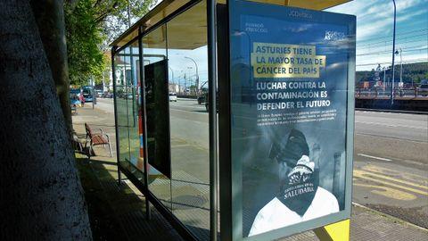 Una de las marquesinas de autobús del Parque del Muelle con uno de los esloganes de Podemos Asturias