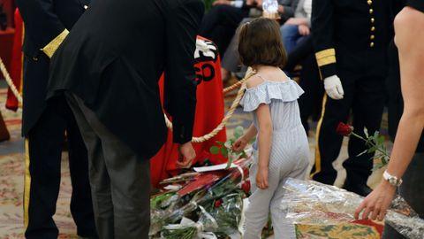 Una niña deposita flores en la capilla ardiente