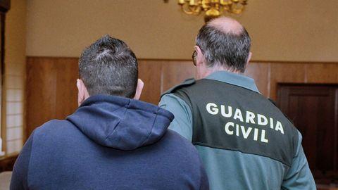 Roberto H.H. custodiado por un guardia civil en la sala de la Audiencia de Valladolid, donde se celebra el juicio