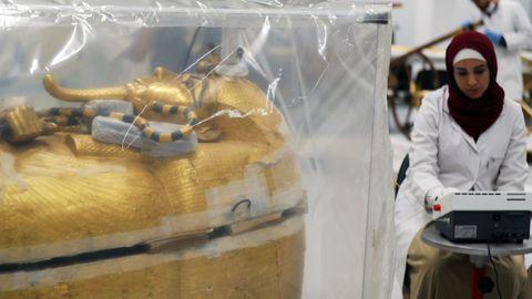 Una arqueóloga trabaja junto al sarcófago de Tutankamón, aislado y esterilizado dentro de una cámara especial.