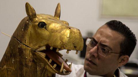 Un arqueólogo trabaja en una figura perteneciente a la cámara funeraria del rey