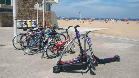 Patinetes eléctricos de uso compartido, aparcados en la playa de Poniente