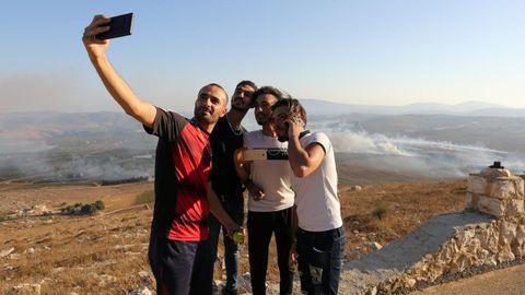 Varios jóvenes se hacen un selfi  La gente se toma selfies en el lugar donde cayeron proyectiles disparados desde Israel en la aldea Maroun al Ras