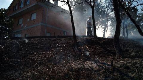 Un vecino de la parroquia de Seoane refresca el suelo quemado en el entorno de una vivienda con una manguera