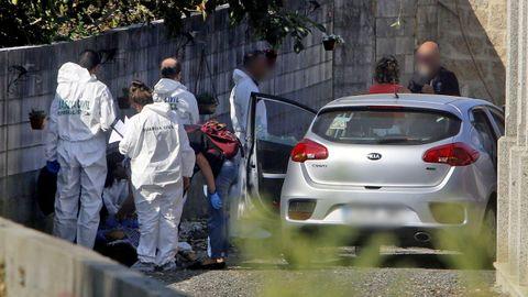 La policía científica trabaja sobre un cadáver junto a un coche