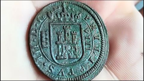 Una moneda de ocho maravedís hallada en el yacimiento de Cereixa. Fue acuñada en 1618, bajo el reinado de Felipe III. A la izquierda del escudo de Castilla está representado el acueducto de Segovia, lo que indica el origen de la pieza