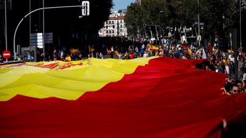 Decenas de personas sostienen la bandera de España de 1.000 metros cuadrados unos 130 kilos de peso, durante la concentración convocada por Vox
