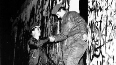 Un guardia de Alemania del Este ayudado por un policía del Berlín Oeste