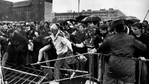 Ciudadanos de la RDA rompen las barricadas colocadas frente a la Puerta de Brandenburgo