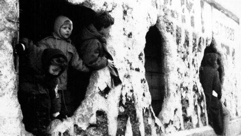 Niños berlineses jugando en los orificios del muro