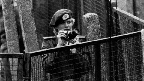 Una soldado de la RDA hace guardia con una cámara