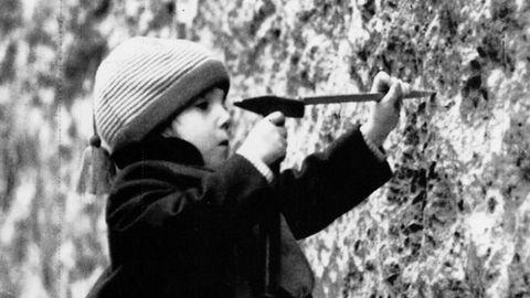 Una niña pica el muro cerca de la Puerta de Brandenburgo