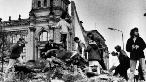 Los niños juegan frente a los escombros del muro frente al edificio Reichstag